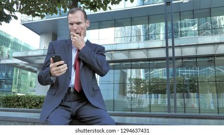 Shocked, Astonished Middle Aged Businessman Using Smartphone