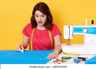 Shocked attractive female opens her mouth widely with surprise, making stitches with chalk on blue piece of fabric, ready to sew new clothes, having lot of ideas to implement. Sewing concept.