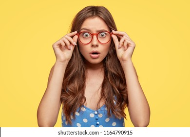 Shocked attractive teenager wears glasses with red rim, polka dot blouse, stares at camera with frightened expression as hears horrified news, poses against yellow background. Omg, its dreadful!