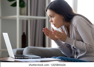 Shocked attractive woman looking with amazement at laptop screen, sitting on sofa at home, cute girl with wide opened eyes watching movie or video in social network, surprised by internet news