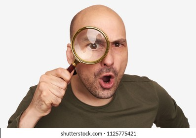 Shocked bald guy looking through the magnifying glass. Isolated on white background