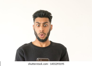 Shocked bearded male model surprised to recieve text message about his bills, realize that he is complete bankrupt, has no money to pay debts. Stunned man reads unexpected news online on mobile phone