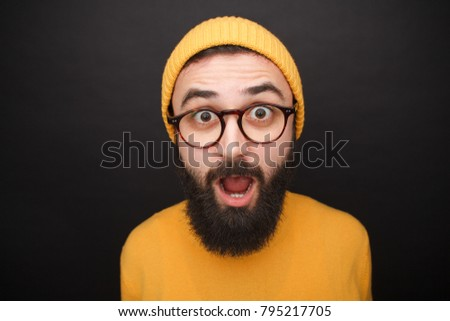 77425db2eb8 Shocked bearded man wearing glasses and yellow clothes on black background.