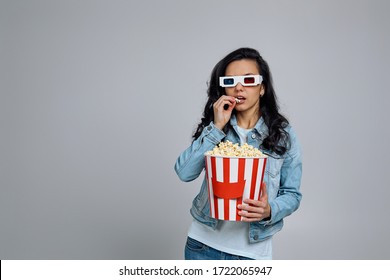 Shocked beautiful caucasian woman wearing red-blue 3d glasses and eating popcorn from bucket while watching a movie isolated on gray background. copy space