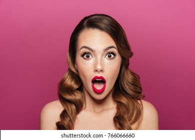 Shocked beautiful lady with opened mouth looking camera isolated over pink