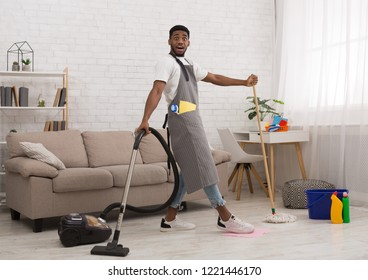 Shocked black guy cleaning house with mop and vacuum cleaner simultaneously, deadline and lack of time concept