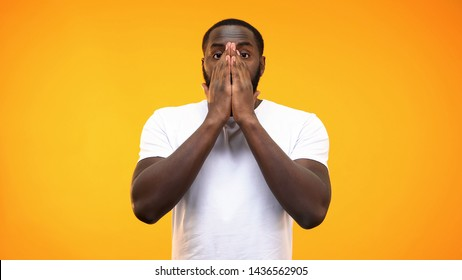 Shocked black male covering face by hands, problem astonishment, amazement