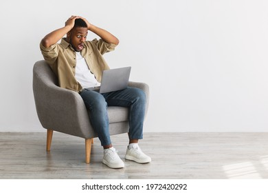 Shocked Black Man Looking At Laptop Computer Having Problem With Internet Connection Working Online Sitting In Chair On Gray Background. Oops, Negative News, Error Concept. Free Space For Text