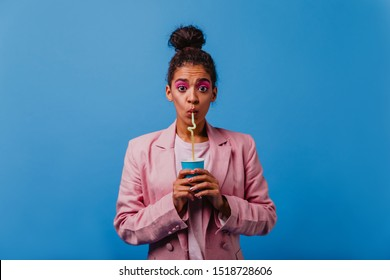 Shocked black woman with dark eyes drinking soda. Indoor photo of surprised african girl with cup of cocktail.