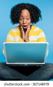 Shocked black woman using laptop computer