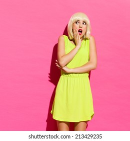Shocked blonde girl in lime dress lean on the wall. Three quarter length studio shot on pink background.