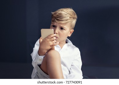 Shocked boy looking at smart phone in disbelief. Surprised child using mobile phone and reading watching something on the internet.