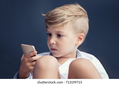 Shocked boy using mobile phone and reading text message. Small boy looking at cell phone in disbelief.