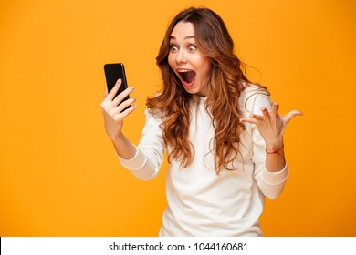 Shocked brunette woman in sweater holding smartphone and rejoices over yellow background