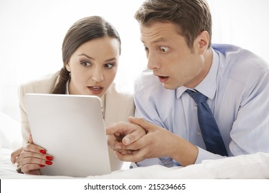 Shocked business couple using digital tablet in hotel