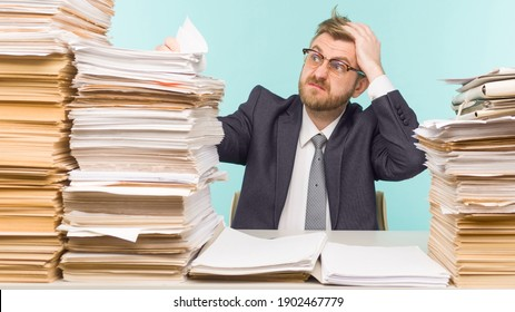 Shocked businessman sitting at the table with many papers in office, he is overloaded with work