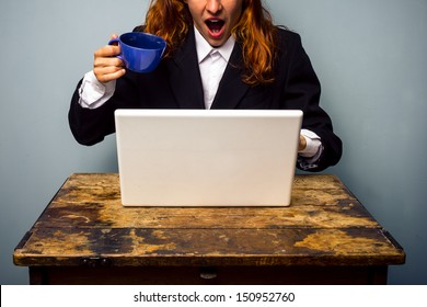 Shocked businesswoman nearly spilling coffee on her laptop