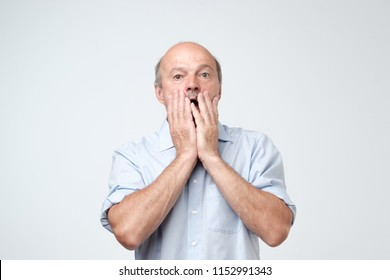 Shocked caucasian man face. He is closing his face with hands. It can not be true concept