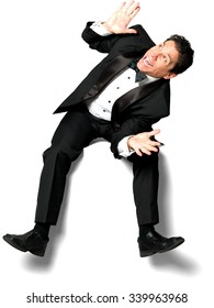 Shocked Caucasian man with short black hair in a tuxedo sitting and defending with body - Isolated