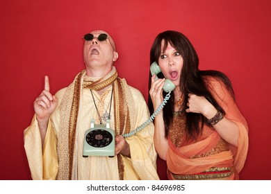 Shocked Caucasian on phone call while bald monk points index finger upward toward heaven