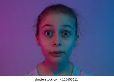 Shocked child girl face - expressive portrait of ten years old kid with eyes wide opened. Colorful light - purple, pink and blue tonal transitions. Dark mysterious mood.