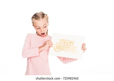 shocked child showing a card with text Merry Christmas, isolated on white