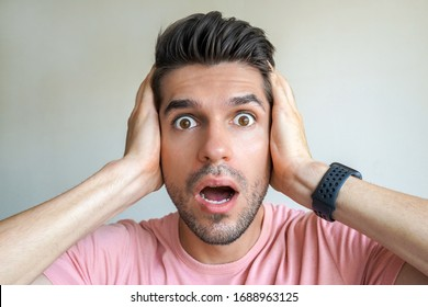 Shocked Closeup Face of a young attractive man holding his head with two arms