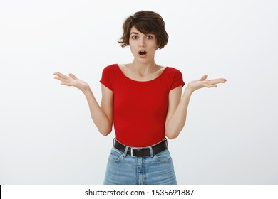 Shocked confused cute european woman short pixie haircut shrugging hands spread sideways gasping shocked stunned news had no idea posing puzzled perplexed answer difficult question white background