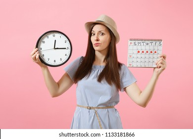 Shocked confused sad woman in blue dress holding round clock, periods calendar for checking menstruation days isolated on trending pink background. Medical gynecological concept. Copy space