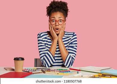 Shocked dark skinned penwoman has deadline for creating masterpiece, forgets about something important, stares through eyewear, poses against pink background near desktop. Terrified female creator