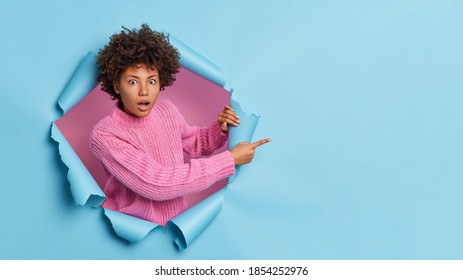 Shocked dark skinned woman with curly hair points away on blank space sees something incredible and breathtaking wears casual knitted sweater breaks through paper background. Omg look there.