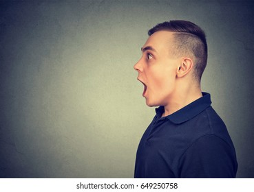 Shocked dazed young man isolated on gray background