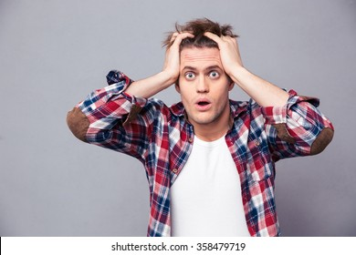 Shocked dazed young man in plaid shirt holding head with both hands over grey background