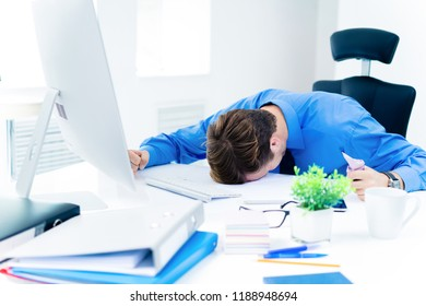 Shocked, distraught or very tired, unhappy businessman in confident blue shirt, working with desktop computer at office. Business, job and education concept.