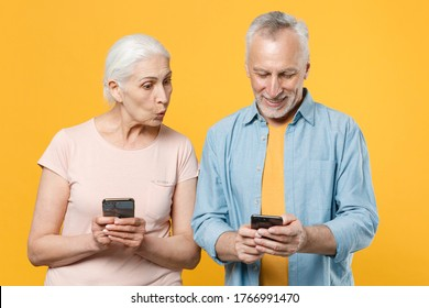 Shocked elderly gray-haired couple woman man in casual clothes isolated on yellow wall background studio portrait. People lifestyle concept. Mock up copy space. Using mobile phone, typing sms message