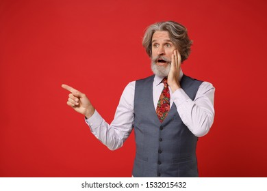 Shocked elderly gray-haired mustache bearded man in classic shirt vest and colorful tie isolated on red background in studio. People lifestyle concept. Mock up copy space. Pointing index finger aside