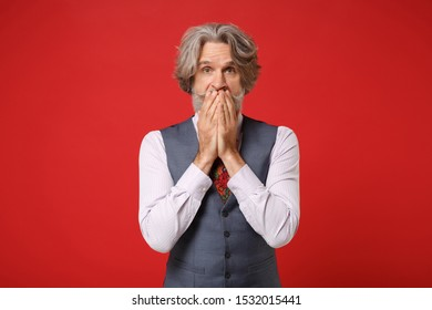 Shocked elderly gray-haired mustache bearded man in classic shirt vest and colorful tie posing isolated on red wall background. People lifestyle concept. Mock up copy space. Covering mouth with hands