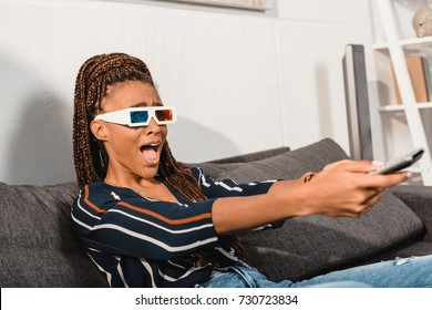 shocked emotional african american woman watching tv in 3d goggles