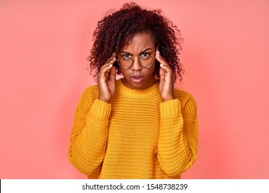 Shocked emotional dark haired woman keeps hands on rim of spectacles, gazes with stupefaction, receives surprising news, models against pink studio wall. Omg, I dont believe you. Reaction concept.