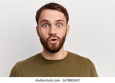 shocked emotional man with bugged eyes and rounded mouth looks at the camera , being amazed to see something unexpected.feeling and emotion, isolated white background