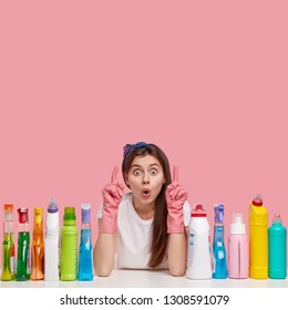 Shocked European housemaid has scared facial expression, dressed in rubber gloves, demonstrates something over copy space, sits at desktop with chemical agents, isolated over pink background.