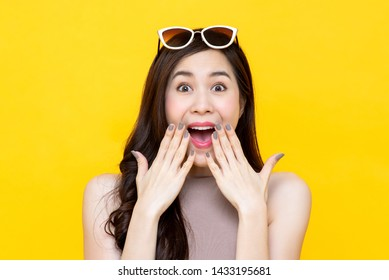 Shocked excited Beautiful Asian woman with mouth open isolated on colorful yellow background