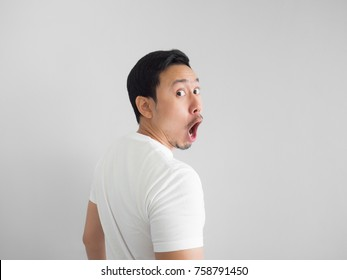 Shocked face of Asian man in white shirt on grey background. Turn around.