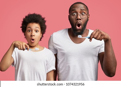 Shocked father and son hold toothbrushes, brush teeth and hurry as late for work or school, overslept, isolated over pink background. Dark skinned African male adult and teenager in bathroom