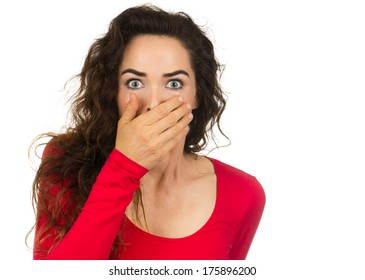 A shocked and frightened woman covering her mouth in surprise and disbelief. Isolated on white.