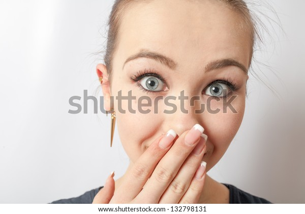 A shocked frightened young girl covering his mouth with his hand and staring wide eyed at the camera. Shot on white background.