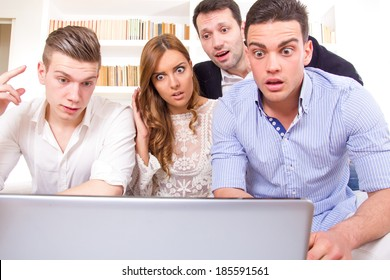 shocked and frustrated casual group of friends sitting on couch looking at laptop, pissed off friends because results, cheering on computer