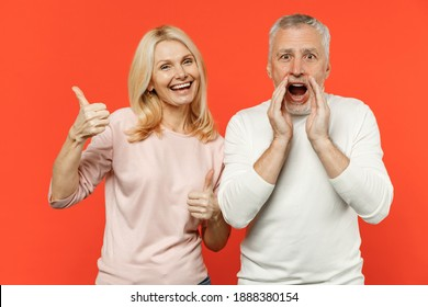 Shocked funny couple friends elderly gray-haired man blonde woman in white pink clothes standing screaming with hands gesture near mouth showing thumb up isolated on orange background studio portrait