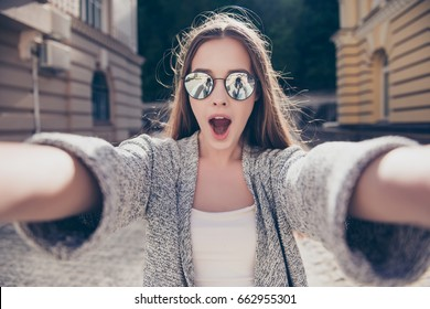 Shocked girl in sunglasses and open mouth is making selfie on a camera. She is wearing casual outfit, walking outdoors at the city