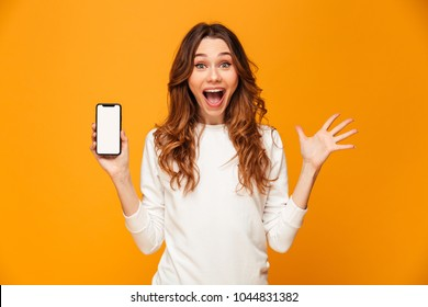 Shocked happy brunette woman in sweater showing blank smartphone screen while looking at the camera over yellow background